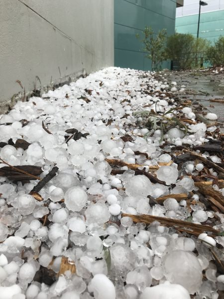 Large hailstones piled up against the wall